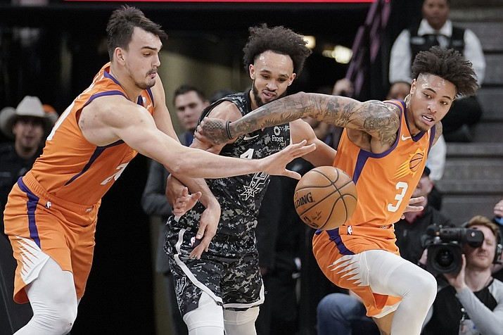 Phoenix Suns' Dario Saric, left, and Kelly Oubre, Jr. (3) fight for possession against San Antonio Spurs' Derrick White during the first half of a game, Friday, Jan. 24, 2020, in San Antonio. (Darren Abate/AP)