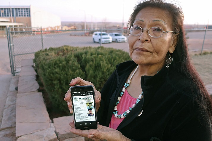 In this Jan. 14, 2020, photo, Margaret Bitsue displays a flier that features her son who she reported missing more than two years ago, in Tuba City, Ariz. Bitsue hasn't seen or heard from Brandon Sandoval, the youngest of her four children, since he went missing. (Felicia Fonseca/AP)