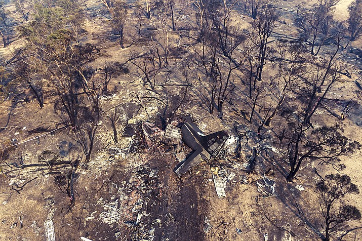 This aerial photo provided by the New South Wales Police, shows wreckage is strewn at the crash site of a firefighting air tanker near Numeralla, south west of Sydney. Three crew from the U.S. were killed when their C-130 Hercules tanker crashed while fighting wildfires in Australia, their employer, Canada-based Coulson Aviation, said in a statement. (NSW Police via AP)