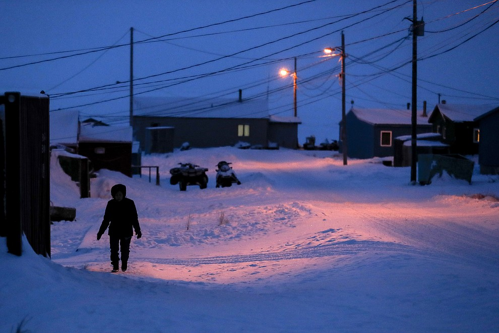 In this Jan. 20, 2020 photo, a woman walks before dawn in Toksook Bay, Alaska, a mostly Yuip'ik village on the edge of the Bering Sea. Census workers traditionally begin the official decennial count in rural Alaska when the ground is still frozen. That allows easier access before the spring melt makes many areas inaccessible to travel and residents scatter to subsistence hunting and fishing grounds. The rest of the nation, including more urban areas of Alaska, begin the census in mid-March. (AP Photo/Gregory Bull)