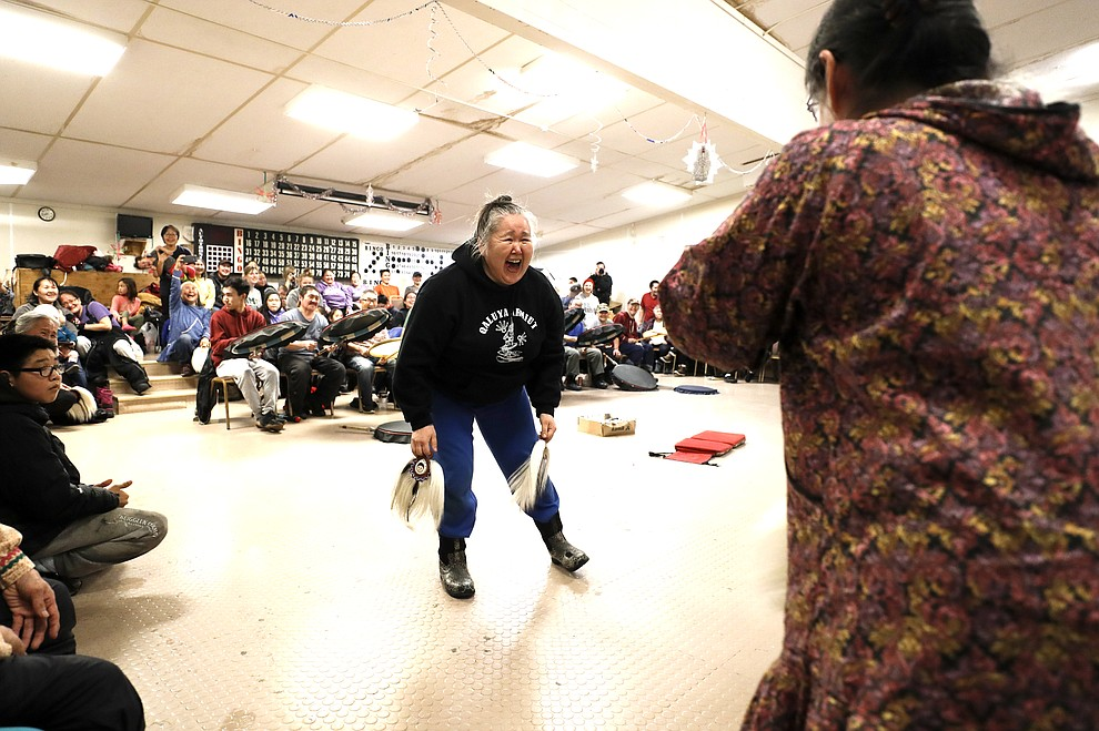 In this Monday, Jan. 20, 2020 photo, Darlene Lincoln, center, laughs as she takes part in an Alaska Native dance in Toksook Bay, Alaska, a mostly Yup'ik village on the edge of the Bering Sea. Census workers traditionally begin the official decennial count in rural Alaska when the ground is still frozen. That allows easier access before the spring melt makes many areas inaccessible to travel and residents scatter to subsistence hunting and fishing grounds. The rest of the nation, including more urban areas of Alaska, begin the census in mid-March. (AP Photo/Gregory Bull)