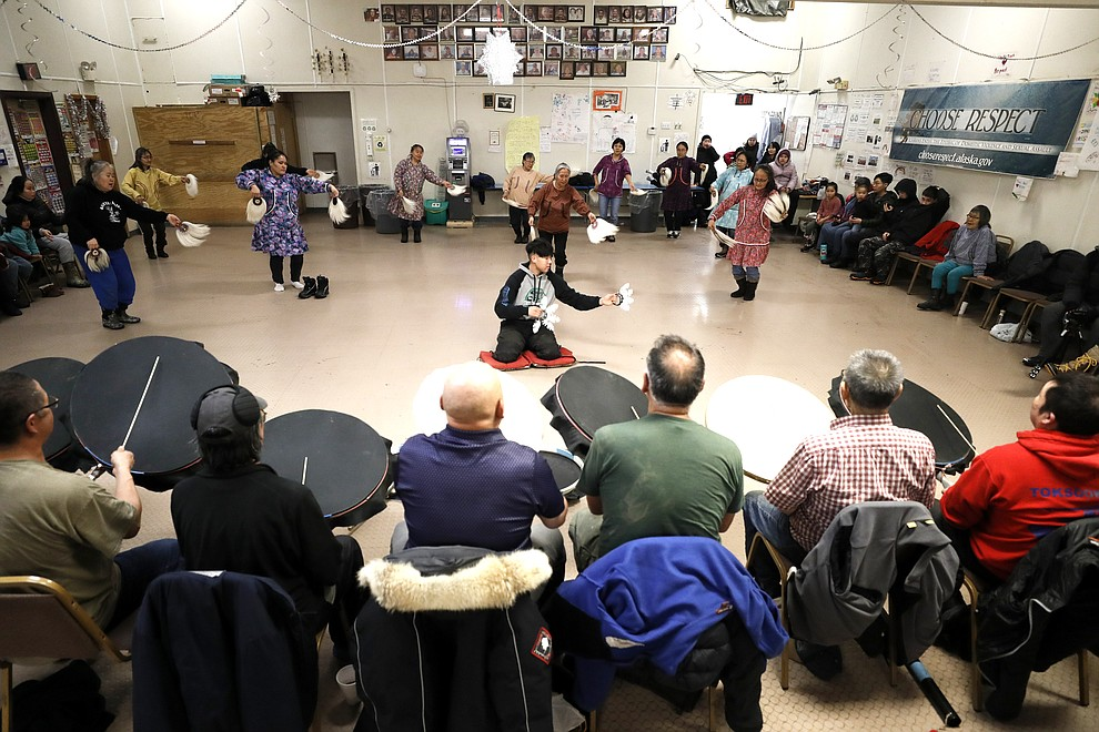 In this Monday, Jan. 20, 2020 photo, people take part in an Alaska Native dance in Toksook Bay, Alaska, a mostly Yup'ik village on the edge of the Bering Sea. Census workers traditionally begin the official decennial count in rural Alaska when the ground is still frozen. That allows easier access before the spring melt makes many areas inaccessible to travel and residents scatter to subsistence hunting and fishing grounds. The rest of the nation, including more urban areas of Alaska, begin the census in mid-March. (AP Photo/Gregory Bull)