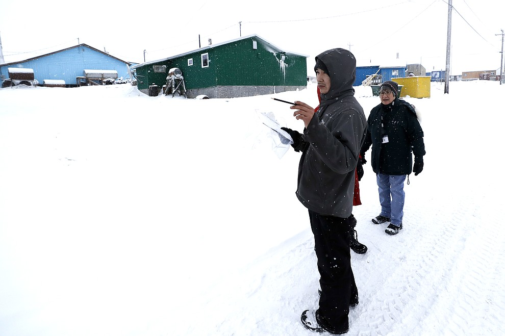 In this Monday, Jan. 20, 2020 photo, census workers verify that their maps match up to the right amount of houses in Toksook Bay, Alaska, a mostly Yup'ik village on the edge of the Bering Sea. Census workers traditionally begin the official decennial count in rural Alaska when the ground is still frozen. That allows easier access before the spring melt makes many areas inaccessible to travel and residents scatter to subsistence hunting and fishing grounds. The rest of the nation, including more urban areas of Alaska, begin the census in mid-March. (AP Photo/Gregory Bull)