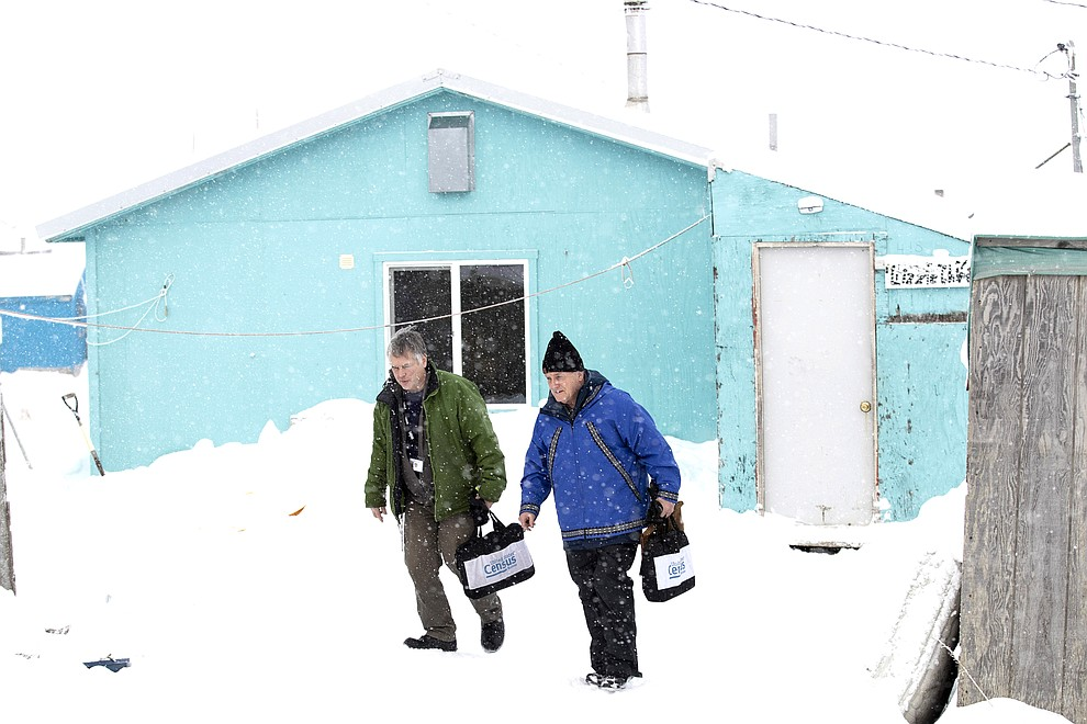 Census bureau director Steven Dillingham, right, walks alongside Census worker Tim Metzger after conducting the first enumeration of the 2020 Census Tuesday, Jan. 21, 2020, in Toksook Bay, Alaska. (AP Photo/Gregory Bull)