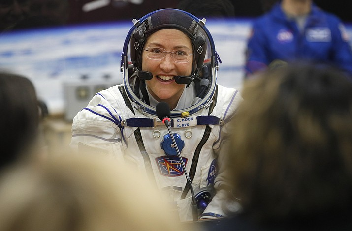 In this Thursday, March 14, 2019 photo, U.S. astronaut Christina Koch, member of the main crew of the expedition to the International Space Station (ISS), speaks with her relatives through a safety glass prior the launch of Soyuz MS-12 space ship at the Russian leased Baikonur cosmodrome, Kazakhstan. Koch told The Associated Press on Tuesday, Jan. 28, 2020, her 319th consecutive day in space - that taking part in the first all-female spacewalk was the highlight of her mission. She's been living on the International Space Station since March and returns to Earth on Feb. 6, landing in Kazakhstan with two colleagues aboard a Russian capsule. (Dmitri Lovetsky/AP, Pool)