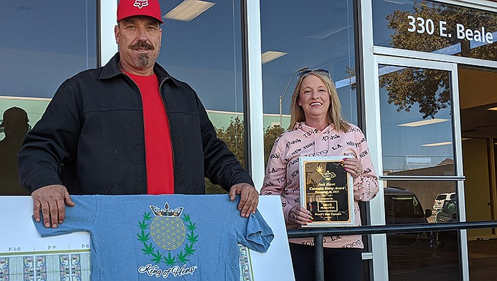 Mike and Tuesday Simmons, who will manage and be frequent faces at Kingman's The King of Hemp Store, pose in front of the chosen location, the old Wells Fargo building in downtown Kingman. (Photo by Travis Rains/Kingman Miner)