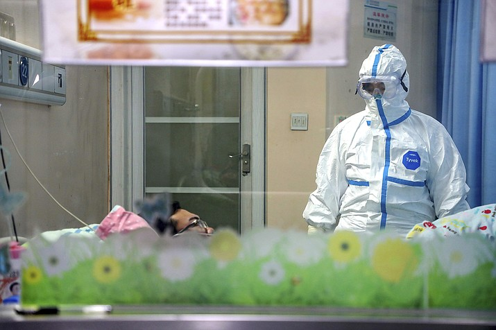 A doctor attends to a patient in an isolation ward at a hospital in Wuhan in central China's Hubei Province, Thursday, Jan. 30, 2020. China counted 170 deaths from a new virus Thursday and more countries reported infections, including some spread locally, as foreign evacuees from China's worst-hit region returned home to medical observation and even isolation. (Chinatopix via AP)