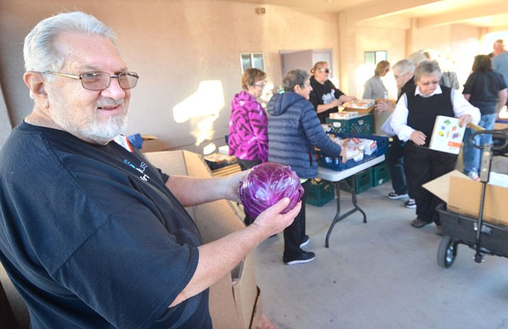 Pastor Randy Sutter distributes heads of cabbage during the Manzanita Outreach food-sharing  event at Vineyard Christian Fellowship Church on Zalesky Road in Bridgeport. About 170 families were served Tuesday. VVN/Vyto Starinskas