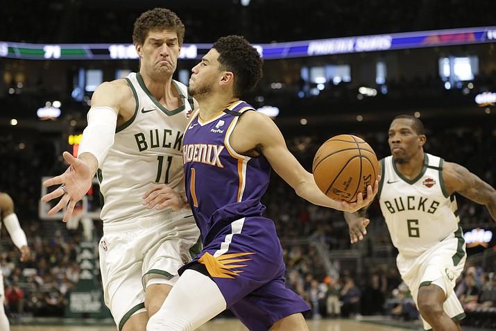 Phoenix Suns' Devin Booker drives against Milwaukee Bucks' Brook Lopez during the second half Sunday, Feb. 2, 2020, in Milwaukee. (Jeffrey Phelps/AP)