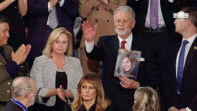 Marsha and Carl Mueller of Prescott, Ariz., parents of Kayla Mueller, a humanitarian aid worker who was killed in 2015 by ISIS, attend President Donald Trump's State of the Union speech Tuesday, Feb. 4, 2020. Carl is holding a photograph of Kayla. (Screen shot from the White House video of the speech)