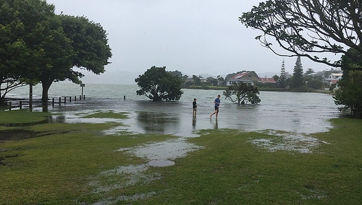 In this Jan. 2019 photo provided by Ben Sheeran shows children play in floodwaters caused by a king tide in Raglan Harbour in Auckland, New Zealand. Amateur scientists are whipping out their smartphones to document the effects of extreme high tides on shore lines from the United States to New Zealand, and by doing so are helping better predict what rising sea levels due to climate change will mean for coastal communities around the world. (Photo by Ben Sheeran/King Tides Auckland)