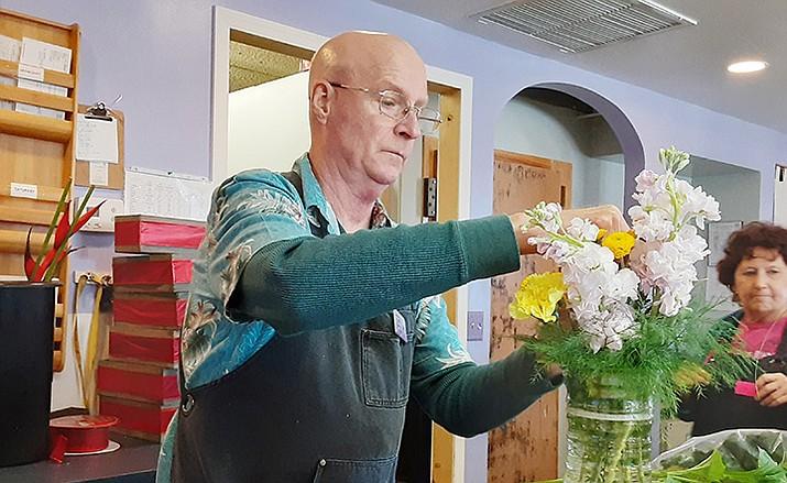 Jim Barry at Allan's Flowers putting an arrangement together. (Jason Wheeler/Courier)