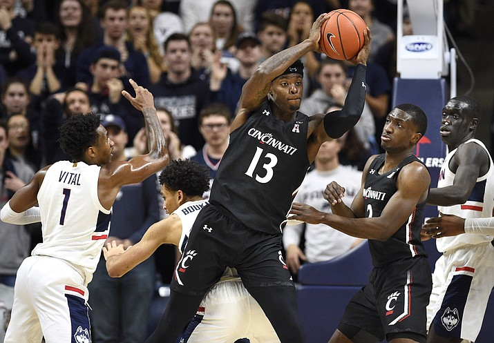 Cincinnati's Tre Scott (13) pulls down a rebound over Connecticut's James Bouknight, bottom, in the first half of an NCAA college basketball game, Sunday, Feb. 9, 2020, in Storrs, Conn. (Jessica Hill/AP)