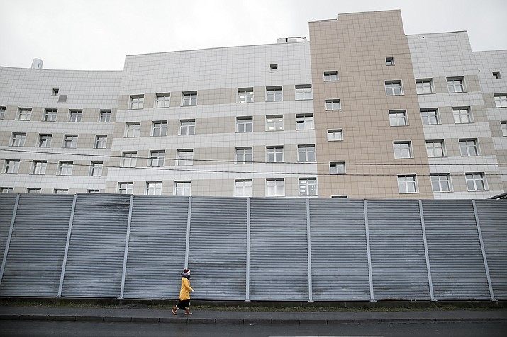 A woman walks past a fence in front of the Botkin hospital in St. Petersburg, Russia, Wednesday, Feb. 12, 2020. A patient has fled the hospital where she was quarantined after coming down with a sore throat after returning to St. Petersburg from Hainan in China. (Dmitri Lovetsky/AP)