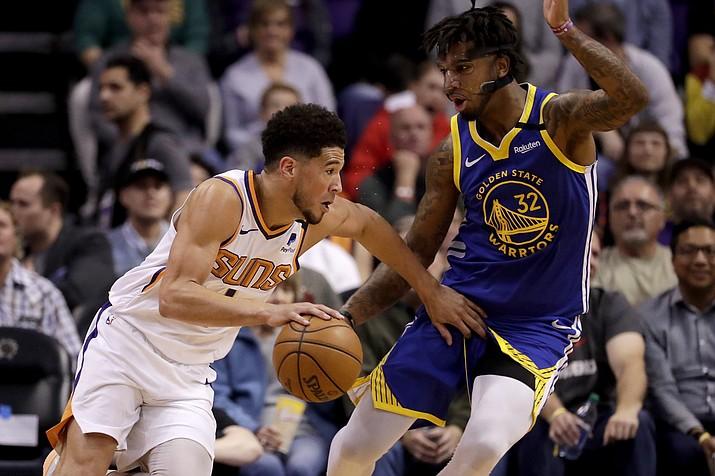 Phoenix Suns guard Devin Booker (1) drives around Golden State Warriors forward Marquese Chriss (32) during the first half of a game, Wednesday, Feb. 12, 2020, in Phoenix. (Matt York/AP)