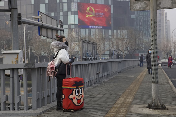 A traveler stands on a bridge near a display showing government propaganda in the fight against the COVID-19 viral illness in Beijing, China Thursday, Feb. 13, 2020. China is struggling to restart its economy after the annual Lunar New Year holiday was extended to try to keep people home and contain novel coronavirus. Traffic remained light in Beijing, and many people were still working at home. (Ng Han Guan/AP)