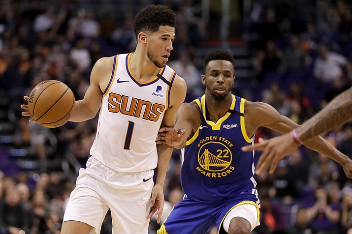 Phoenix Suns guard Devin Booker (1) looks to pass as Golden State Warriors guard Andrew Wiggins (22) defends during the second half of a game, Wednesday, Feb. 12, 2020, in Phoenix. (Matt York/AP)