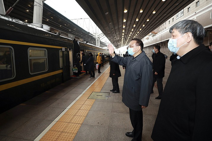 In this Friday, Feb. 14, 2020 photo, Chinese Premier Li Keqiang, second from right, greets travelers arriving at Beijing West Railway Station in Beijing. China reported Saturday a figure of 2,641 new virus cases, a major drop from the higher numbers in recent days since a broader diagnostic method was implemented. (Ding Lin/Xinhua via AP)