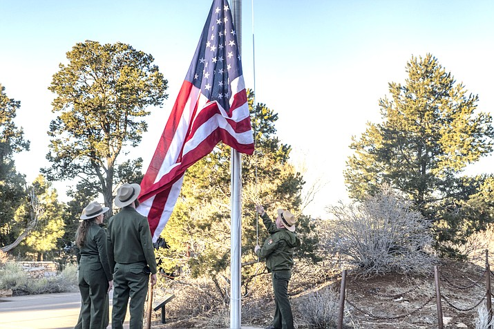National Park Service employees Jill Staurowsky, Rader Lane and Jeremy Childs lower the flag Feb. 12 at the Grand Canyon Visitor's Center in honor of NPS Ranger Ron Brown. (Veronica R. Tierney/WGCN)