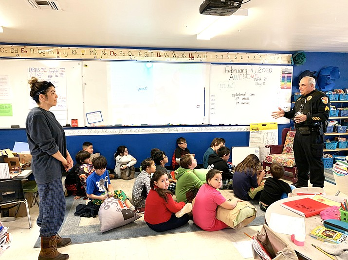 Williams Police Officer Tad Wygal reads to students Feb. 11 for Spirit Week at Heritage Elementary School.(Photos/Heritage Elementary, Loretta McKenney)