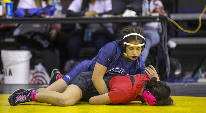 Genesis Higuera of the Odyssey Institute (top) holds down Sara Schmoker of Liberty High School in the 135-pound girls wrestling state championship match. Ten individual state champions were crowned. (Photo by Travis Whittaker/Cronkite News)