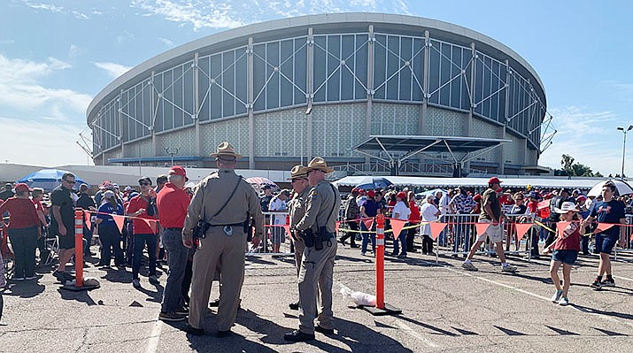 Arizona State Troopers watch the crowd gather outside Arizona Veterans Memorial Coliseum in advance of President Donald Trump's rally Wednesday in Phoenix. (Photo by Jordan Elder/Cronkite News)