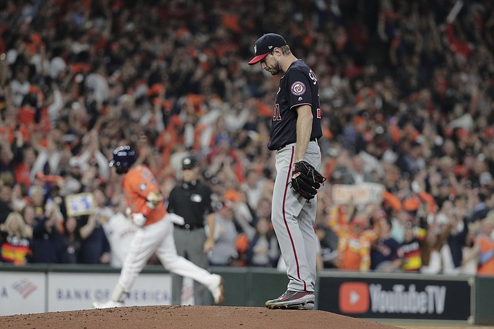 In this Oct. 30, 2019, file photo, Houston Astros' Yuli Gurriel hits a home run off Washington Nationals starting pitcher Max Scherzer during the second inning of Game 7 of the World Series in Houston. The last time these teams played the Nationals were celebrating their World Series title in Houston. Since then the Astros have become the league's villains, with a sign-stealing scandal tarnishing their reputation and casting a shadow on their 2017 title. (David J. Phillip/AP, File)