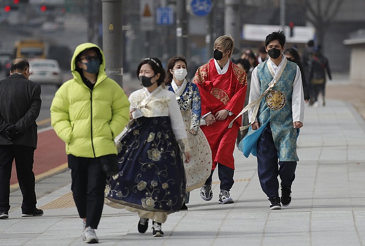 Visitors wearing face masks walk near the Gwanghwamun, the main gate of the 14th-century Gyeongbok Palace, and one of South Korea's well-known landmarks, in Seoul, South Korea, Saturday, Feb. 22, 2020. South Korea's Vice Health Minister Kim Gang-lip says the outbreak has entered a serious new phase but expressed cautious optimism that it can be contained to the region surrounding Daegu, where the first case was reported on Tuesday. (Lee Jin-man/AP)