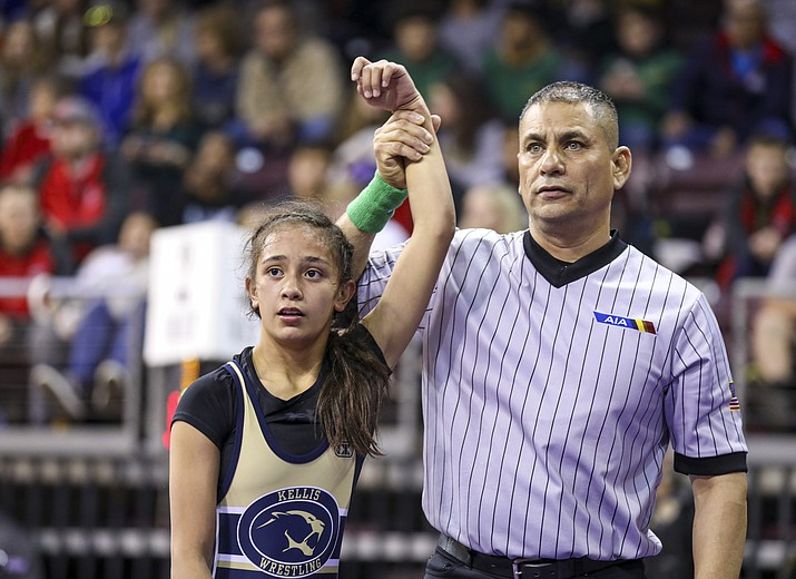 Erica Pastoriza of Raymond S. Kellis High School in Glendale has her arm raised by an official after capturing third place in the 101-pound weight class at the 2020 AIA Girls Wrestling State Championships. The amount of girls wrestling in Arizona has almost doubled in one year. (Travis Whittaker/Cronkite News)