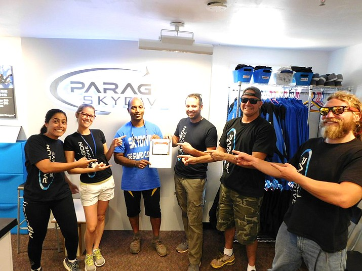 Jason Theuma (center) holds up a skydiving certificate after a completed jump. (Photo courtesy of Paragon Skydiving)