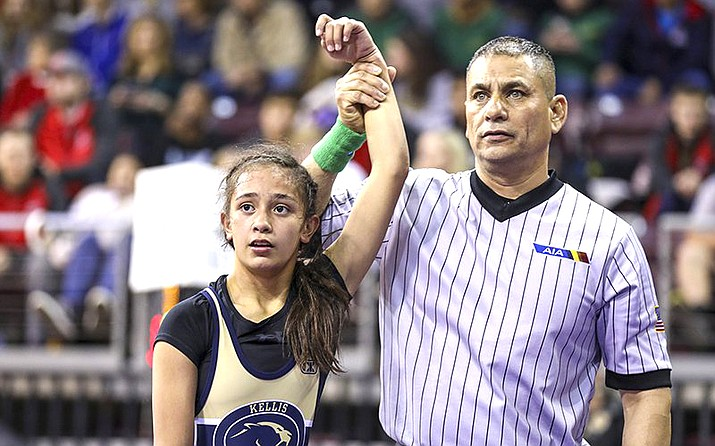 Erica Pastoriza of Raymond S. Kellis High School in Glendale has her arm raised by an official after capturing third place in the 101-pound weight class at the 2020 AIA Girls Wrestling State Championships. (Travis Whittaker/Cronkite News)