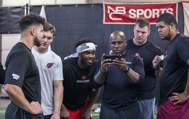 Athletes training for the 2020 NFL combine in Indianapolis review footage with trainer Dwight Pete at the Fischer Institute. (Photo by Travis Whittaker/Cronkite News)