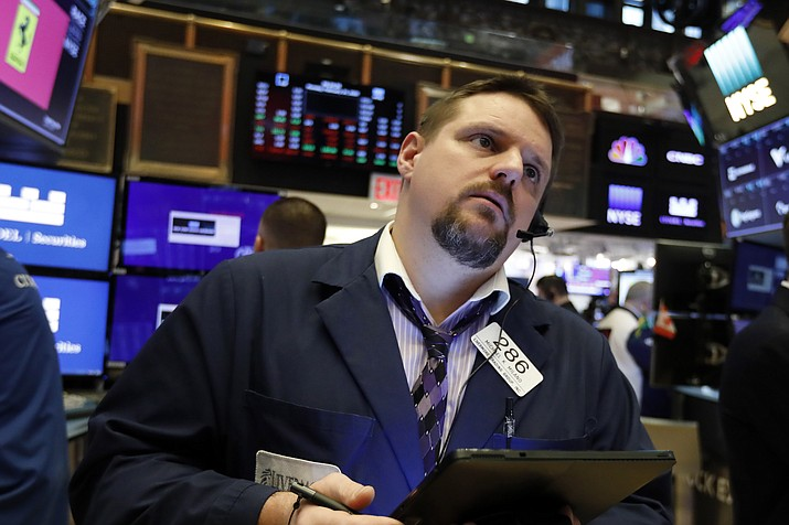 In this Feb. 24, 2020, file photo trader Michael Milano works on the floor of the New York Stock Exchange. Stocks went on a wild ride Thursday as investors struggle to gauge the potential impact of the coronavirus outbreak on the global economy. (AP Photo/Richard Drew, File)