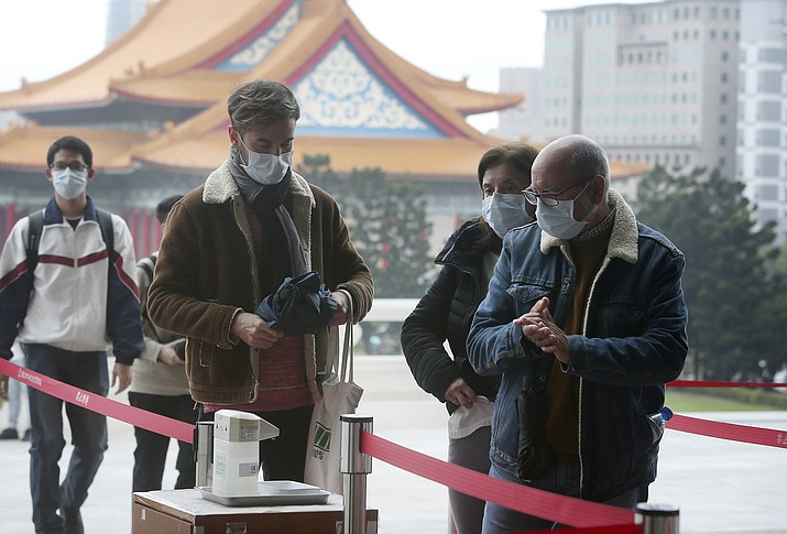 People wear face masks to protect against the spread of the new coronavirus as they visit the Chiang Kai-shek Memorial Hall in Taipei, Taiwan, Thursday, Feb. 27, 2020. As the worst-hit areas of Asia continued to struggle with a viral epidemic, with hundreds more cases reported Thursday in South Korea and China, worries about infection and containment spread across the globe. (Chiang Ying-ying/AP)