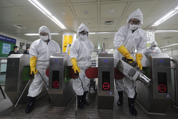 Workers wearing protective gears spray disinfectant as a precaution against the new coronavirus at a subway station in Seoul, South Korea, Friday, Feb. 28, 2020. Japan's schools prepared to close for almost a month and entertainers, topped by K-pop superstars BTS, canceled events as a virus epidemic extended its spread through Asia into Europe and on Friday, into sub-Saharan Africa. (Ahn Young-joon/AP)