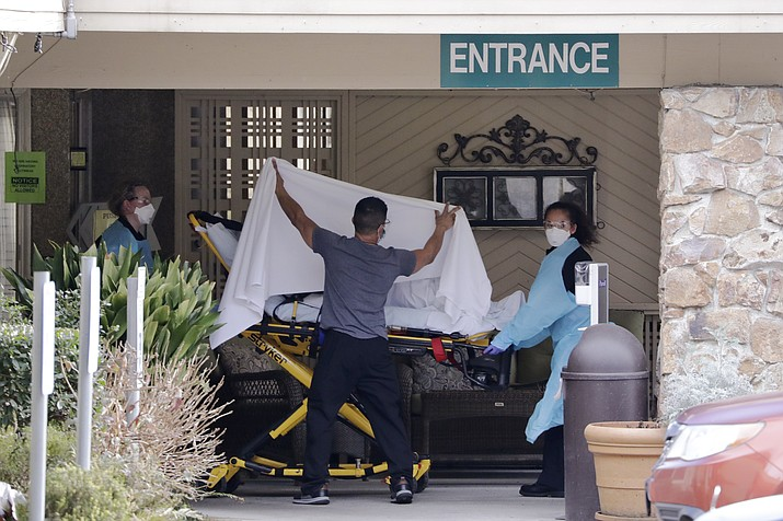 A person is taken by stretcher to a waiting ambulance from a nursing facility where more than 50 people are sick and being tested for the COVID-19 virus, Saturday, Feb. 29, 2020, in Kirkland, Wash. (Elaine Thompson/AP)