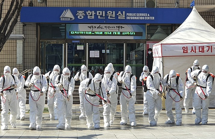 South Korean soldiers wearing protective suits spray disinfectant to prevent the spread of a new coronavirus in front of the Daegu city hall in Daegu, South Korea, Monday, March 2, 2020. (Choi Soo-ho/Yonhap via AP)