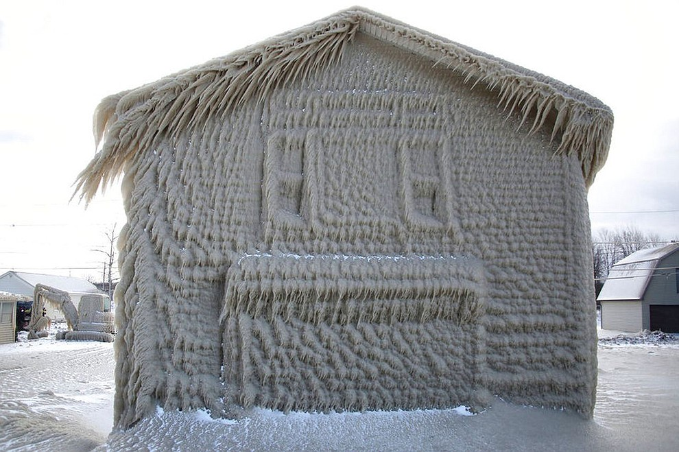 Houses along Hoover Beach are covered by ice from high winds and 15-foot Lake Erie waves, Saturday, Feb. 29, 2020, in Hamburg N.Y. (AP Photo/Jeffrey T. Barnes)