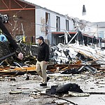 A man walks past storm debris following a deadly tornado Tuesday, March 3, 2020, in Nashville, Tenn. Tornadoes ripped across Tennessee early Tuesday, shredding buildings and killing multiple people. (AP Photo/Mark Humphrey)