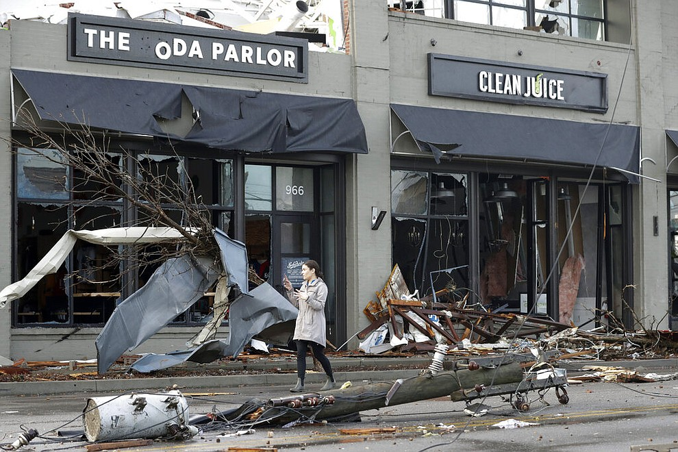 A woman walks past buildings damaged by storms Tuesday, March 3, 2020, in Nashville, Tenn. Tornadoes ripped across Tennessee early Tuesday, shredding buildings and killing multiple people. (AP Photo/Mark Humphrey)