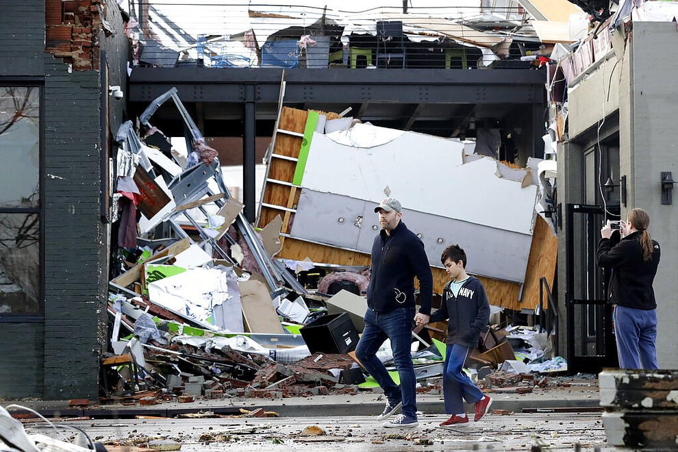 People walk past buildings damaged by storms Tuesday, March 3, 2020, in Nashville, Tenn. Tornadoes ripped across Tennessee early Tuesday, shredding buildings and killing multiple people.  (AP Photo/Mark Humphrey)