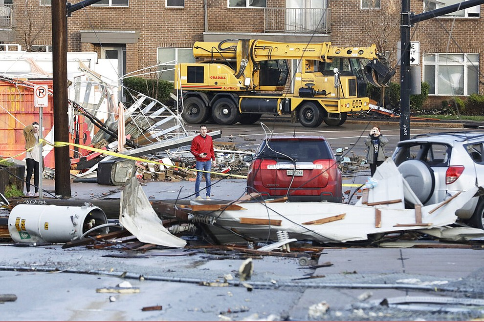 People look over storm damage Tuesday, March 3, 2020, in Nashville, Tenn. Tornadoes ripped across Tennessee early Tuesday, shredding buildings and killing multiple people. (AP Photo/Mark Humphrey)