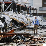 A man looks over buildings destroyed by storms Tuesday, March 3, 2020, in Nashville, Tenn. Tornadoes ripped across Tennessee early Tuesday, shredding buildings and killing multiple people. (AP Photo/Mark Humphrey)
