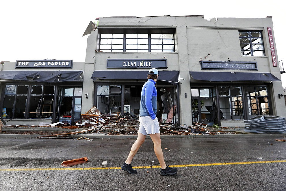 A man walks by buildings destroyed by storms Tuesday, March 3, 2020, in Nashville, Tenn. Tornadoes ripped across Tennessee early Tuesday, shredding buildings and killing multiple people. (AP Photo/Mark Humphrey)
