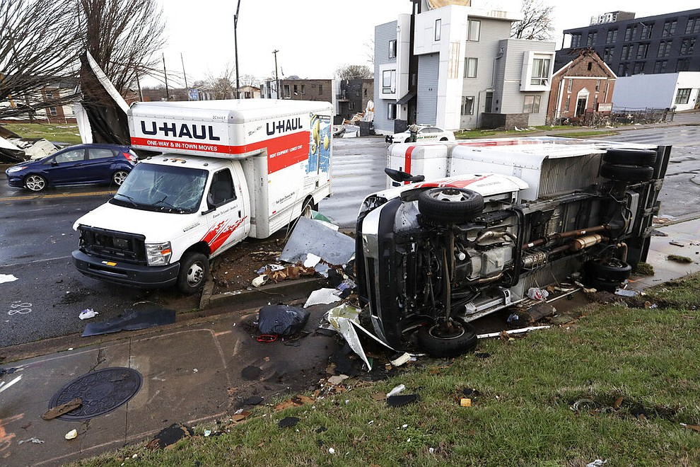 Damaged trucks sit on a sidewalk as well as the street following a deadly tornado, Tuesday, March 3, 2020, in Nashville, Tenn. Tornadoes ripped across Tennessee early Tuesday, shredding buildings and killing multiple people.  (AP Photo/Mark Humphrey)