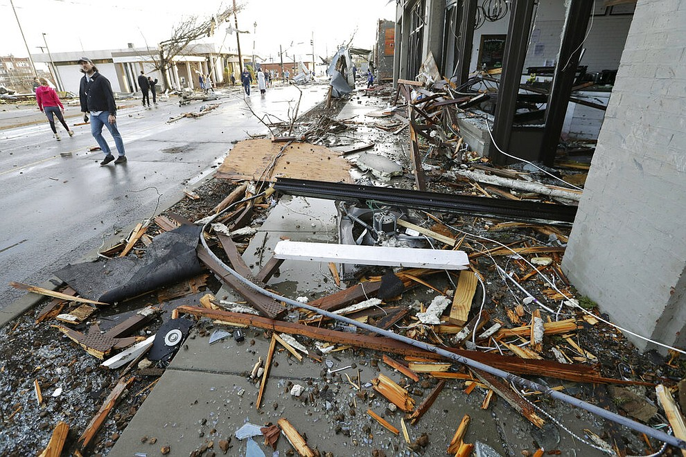 People pass by businesses destroyed by storms Tuesday, March 3, 2020, in Nashville, Tenn. Tornadoes ripped across Tennessee early Tuesday, shredding buildings and killing multiple people.  (AP Photo/Mark Humphrey)