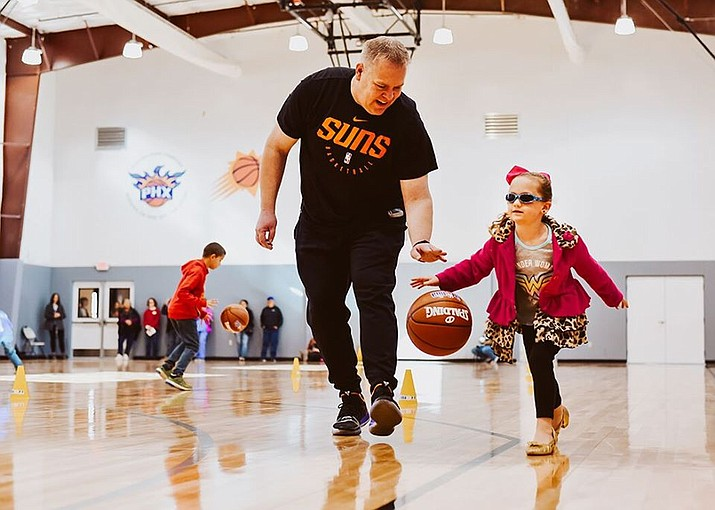 A Northern Arizona Suns coach works with a little girl during a basketball camp in late November 2019 at the Boys & Girls Club in Prescott Valley. (Shana Oh/Courtesy)