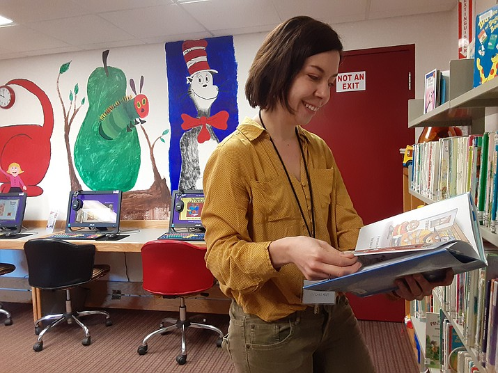 Chino Valley Youth Librarian Rebecca Laurence looks at one of the children's books in the library that she could possibly use for an upcoming storytime Thursday morning, Feb. 27. (Jason Wheeler/Review)