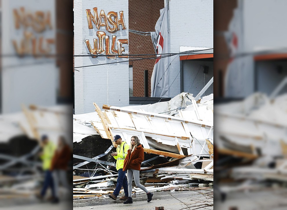 People walk past storm debris following a deadly tornado, Tuesday, March 3, 2020, in Nashville, Tenn. Tornadoes ripped across Tennessee early Tuesday, shredding buildings and killing multiple people. (AP Photo/Mark Humphrey)