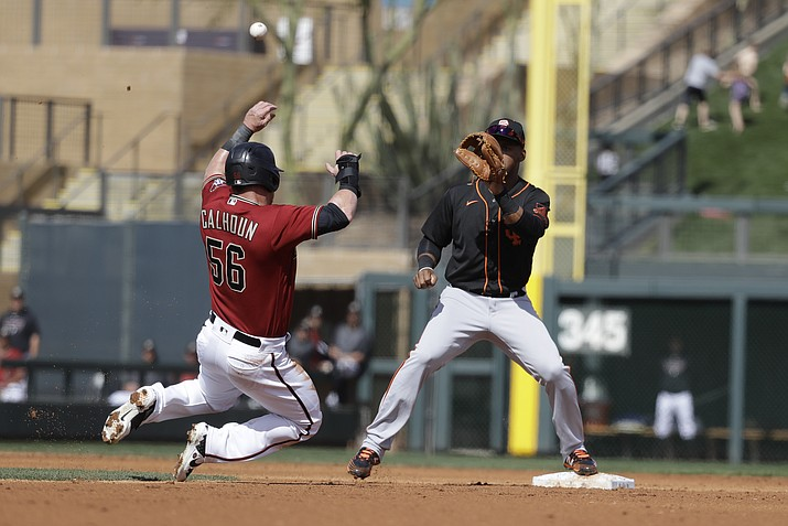 Arizona Diamondbacks' Kole Calhoun is tagged out at second as San Francisco Giants' Abiatal Avelino waits for the throw during the second inning of a spring training game, Monday, March 2, 2020, in Scottsdale. (Darron Cummings/AP)